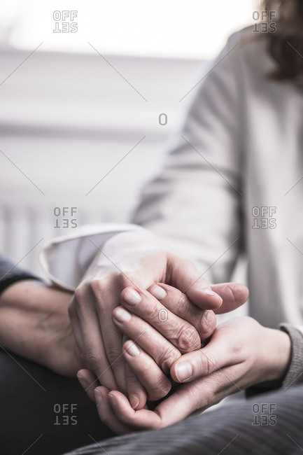 Hands of a health worker comforting an elderly woman