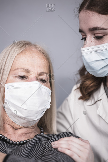 Young healthcare worker comforting a senior woman who is alone during the coronavirus pandemic