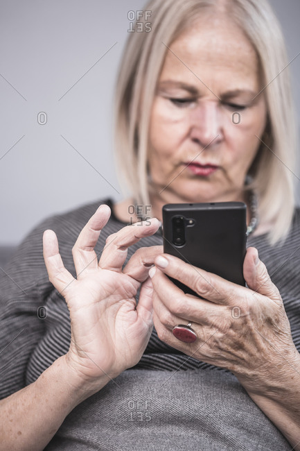 An elderly woman texting on her cell phone