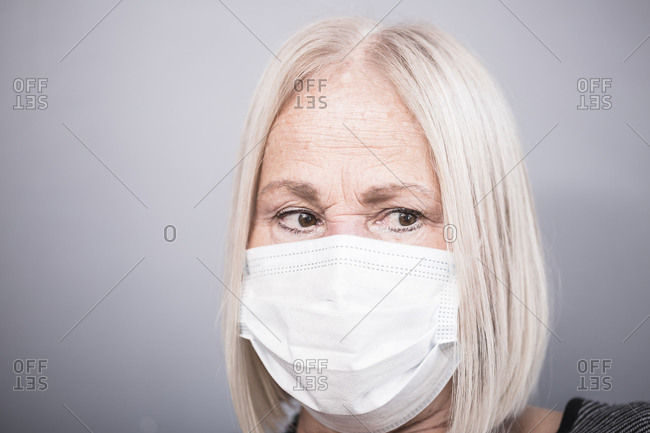 Portrait of an elderly woman wearing a white facemask during a pandemic