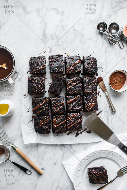 Chocolate zucchini brownies drizzled with sauce and sliced into squares on a white marble counter