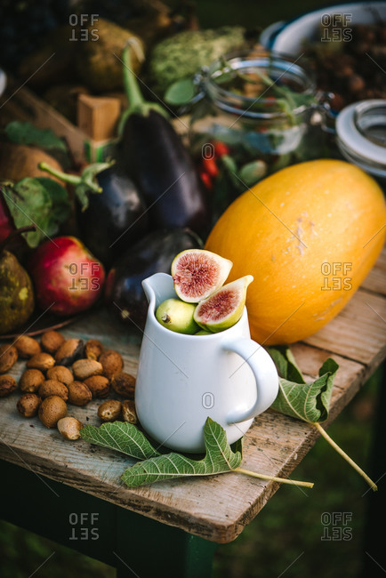 Freshly harvested fruits, vegetables and nuts on a rustic wooden table outdoors