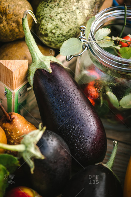Close up of eggplants and other veggies on a rustic wooden table outdoors