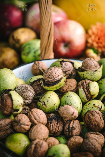 Freshly harvested walnuts in a bowl with fruit in the background