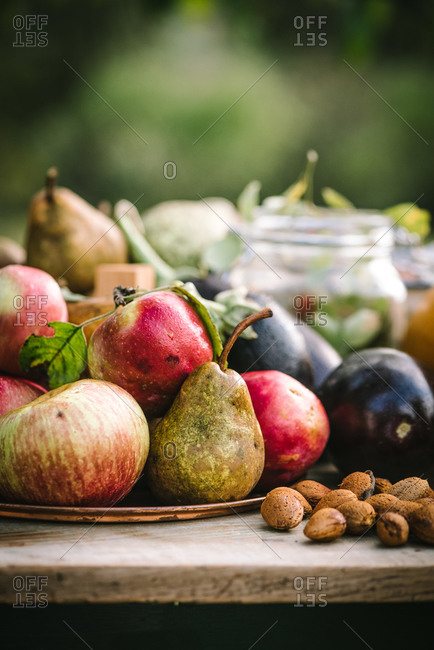 Pecans, eggplant and fruit on a rustic wooden table outdoors