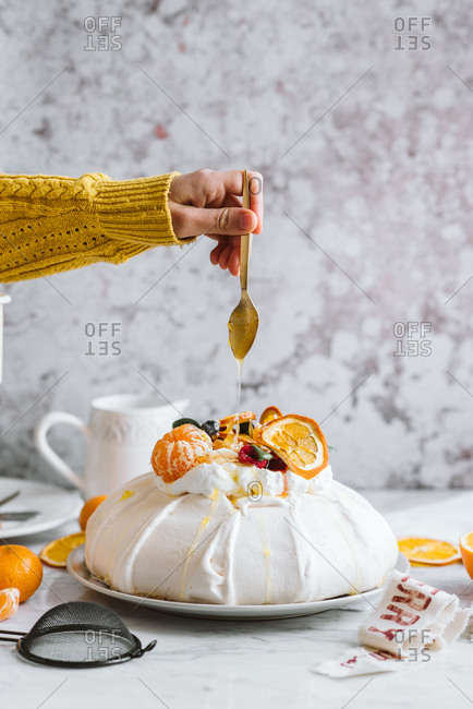 Hand drizzling sauce over a pavlova with oranges