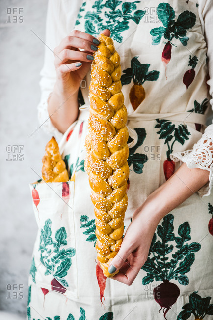 Baker holding a long braided bread loaf