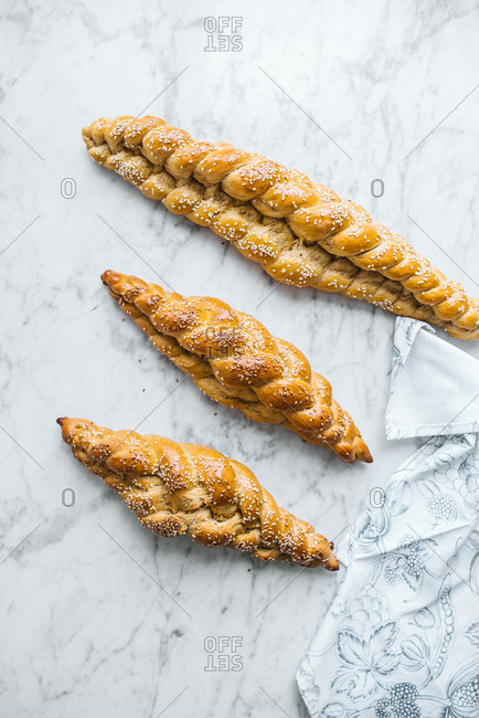 Three long braided sesame seed bread loaves viewed from above