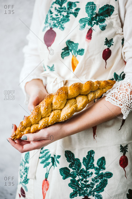 Woman holding a long braided bread loaf