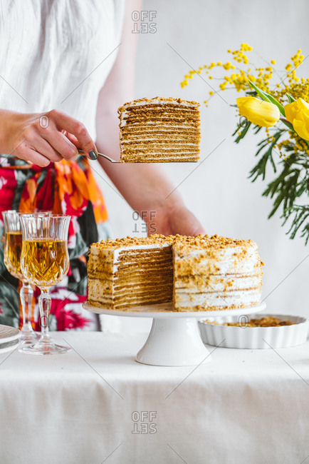 Woman serving a slice of traditional Marlenka a honey layered cake on table