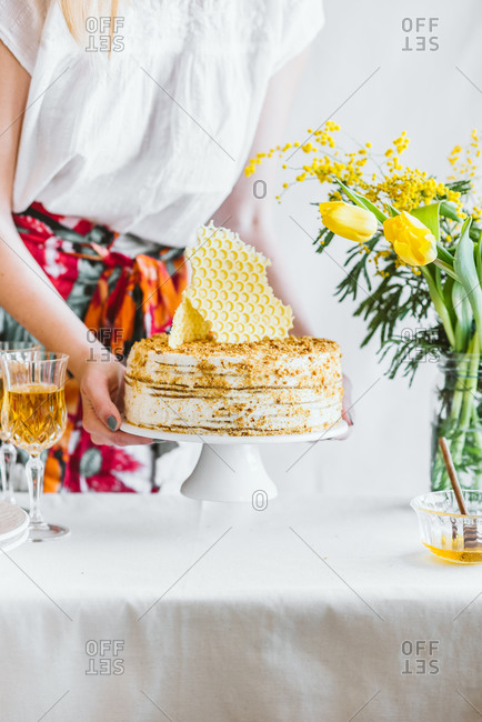 Woman serving a traditional Marlenka a honey layered cake on table