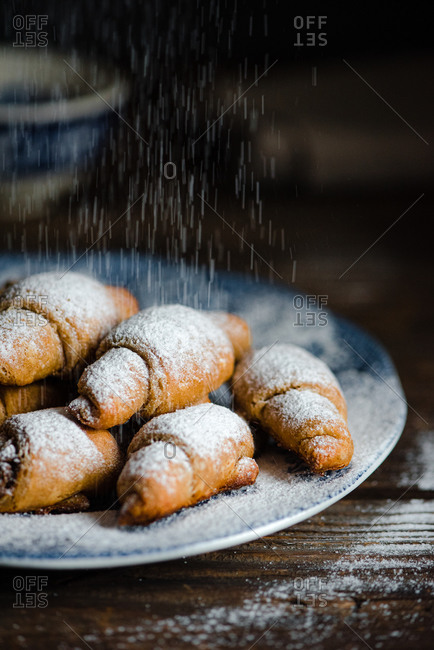 Mini buckwheat croissants being sprinkled with powdered sugar