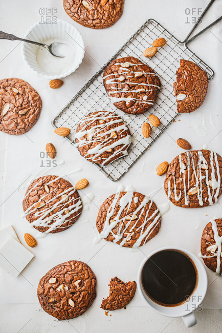 Top view of chocolate cookies with almonds and drizzle and coffee