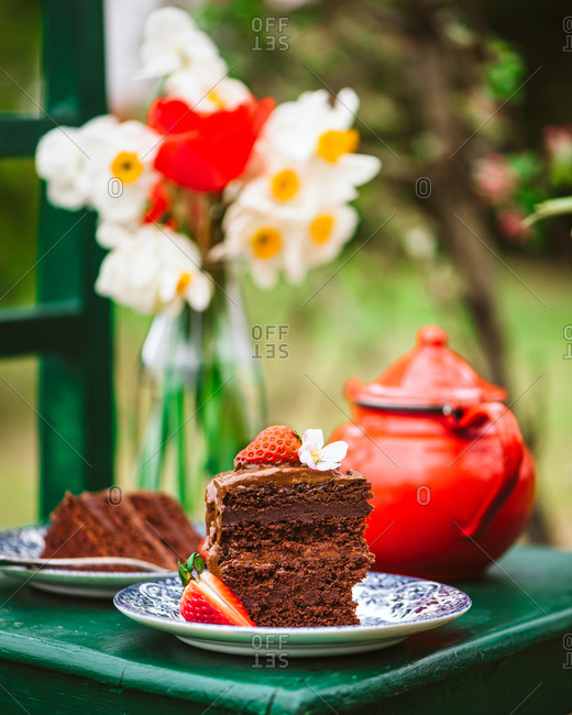 Slice of chocolate cake topped with strawberries on a green chair outdoors