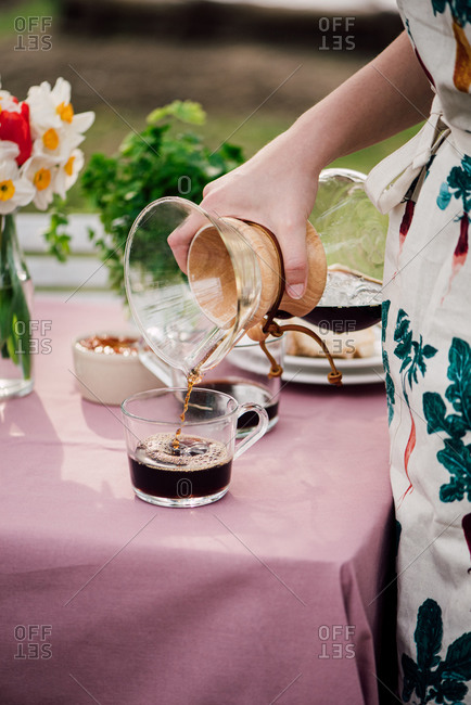 Woman pouring coffee into glass mug from pour-over carafe