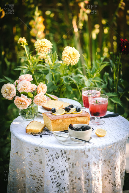 Cake topped with blackberries and lemon on a garden table with peonies