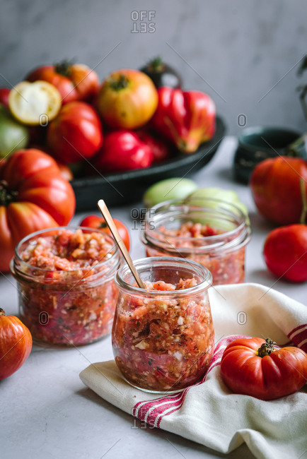 Homemade salsa prepared in glass jars with colorful tomatoes in background