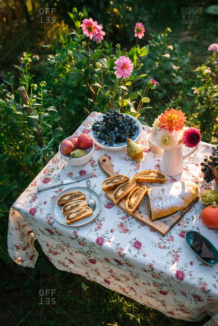 Overhead view of fruit on a garden table with a homemade loaf of dessert bread