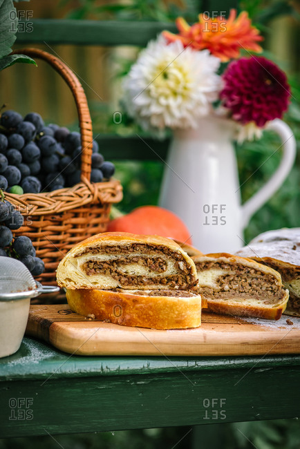 Loaf of dessert bread beside a basket of grapes on a green chair outdoors