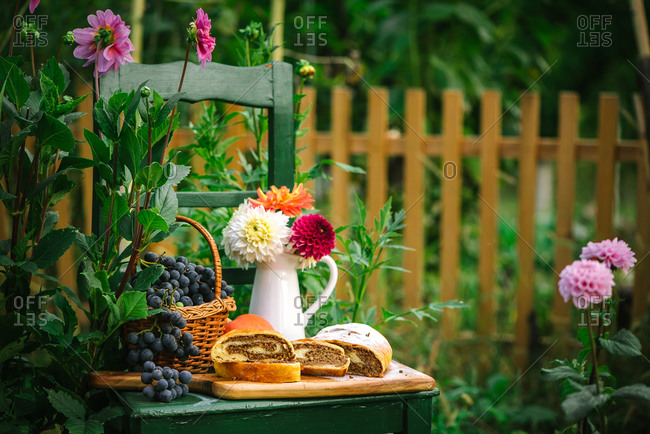 Dessert bread and a basket of grapes on a green chair outdoors