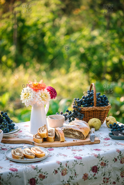 Fruit on a garden table with a homemade loaf of dessert bread and flowers