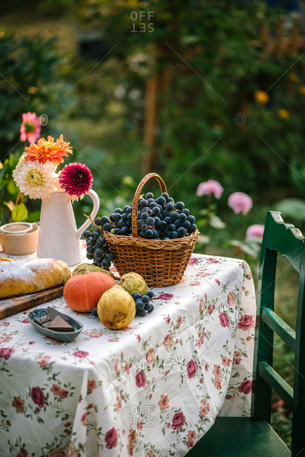 Fruit on a garden table with flowers beside a homemade loaf of dessert bread