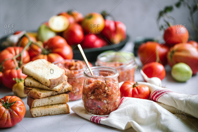 Homemade salsa in glass jars beside a stack of bread and colorful tomatoes