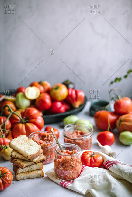 Colorful homegrown tomatoes surround jars with homemade salsa and bread