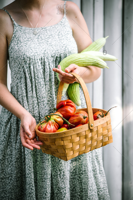 Woman holding basket with freshly harvested fruits and vegetables
