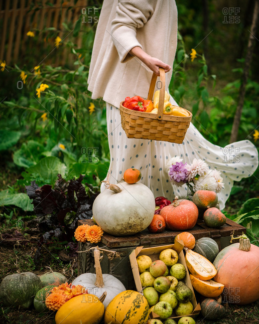 Woman walking in a garden with a basket of freshly harvested produce