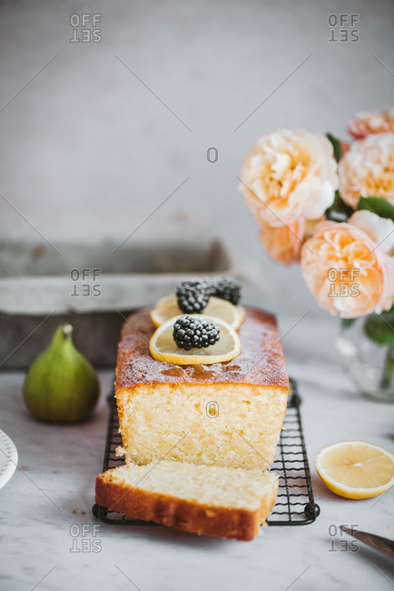 Close up of cake topped with blackberries and lemon on a cooling rack on marble counter