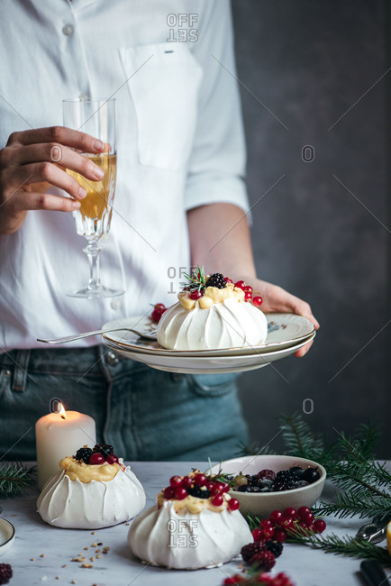 Person holding a glass of champagne and a mini pavlova with berries on top