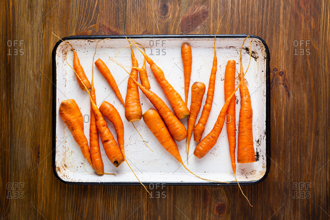 Overhead view of small carrots preparing for roast