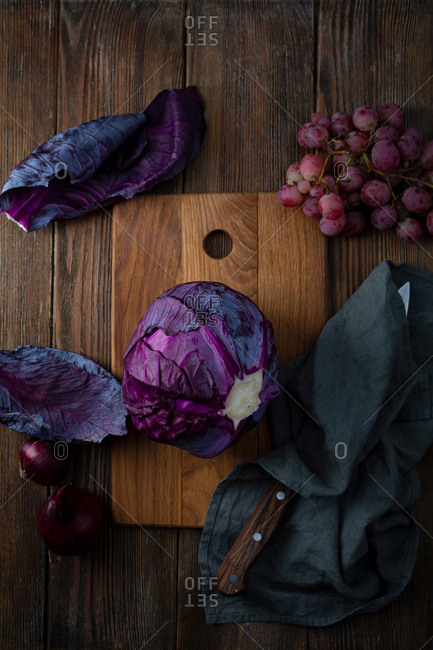 Raw red cabbage with grapes and onions on wooden surface