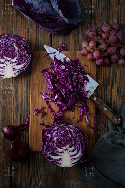 Raw red cabbage being sliced with grapes and onions on wooden surface