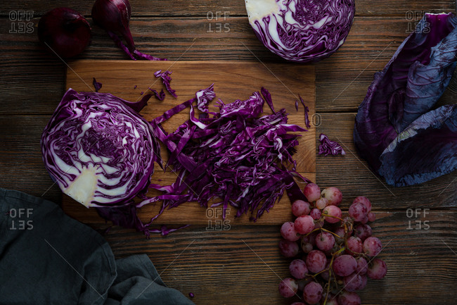 Raw chopped red cabbage with grapes on wooden surface