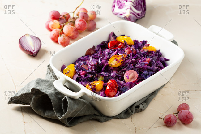 Close up of roasted red cabbage with grapes in white dish on marble surface