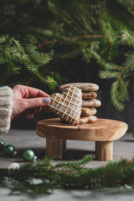 Female hand hold heart shaped cookie on table with pine branches on background