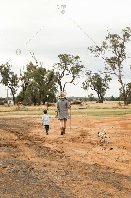 Mother walking hand in hand with her toddler boy on a farm