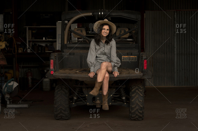 Brunette woman sitting in back of farming vehicle parked in a barn