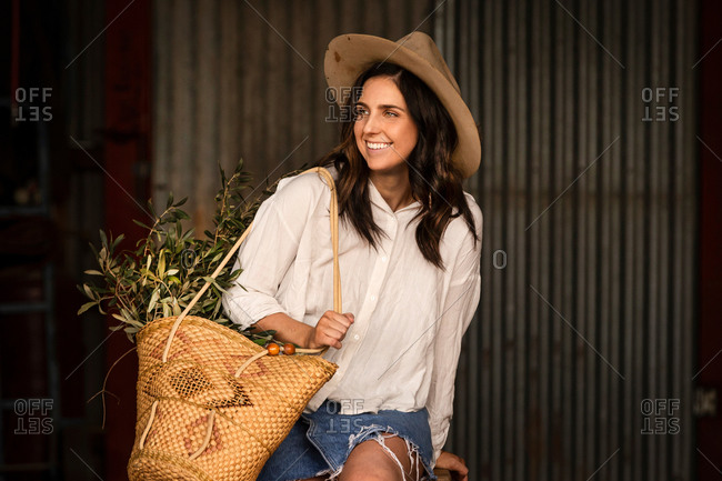 Smiling brunette woman with a basket filled with leafy plants sitting in a barn