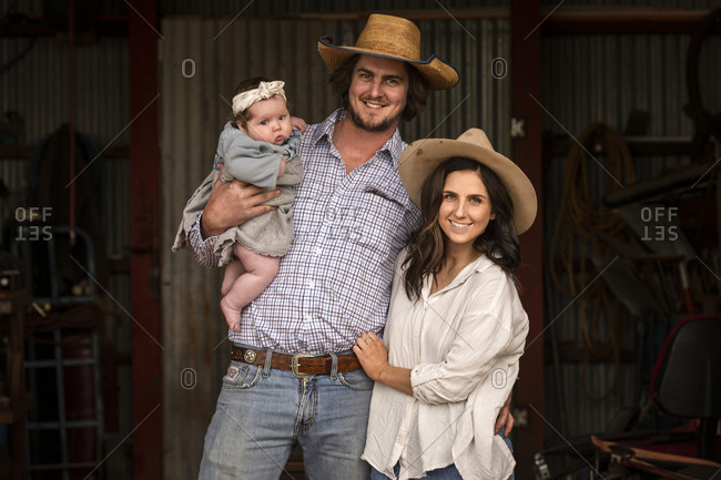 Young husband and wife standing together in barn with their baby girl