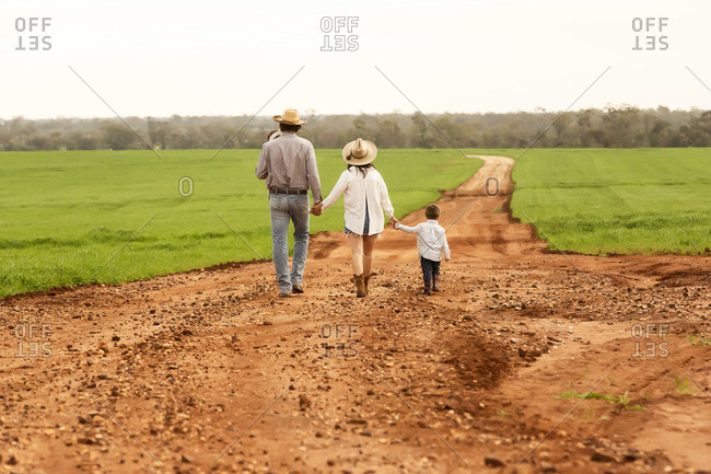 Young family walking hand in hand on a dirt path