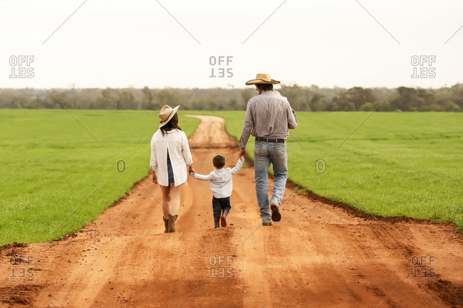 A family walking hand in hand on down a dirt road wearing cowboy hats