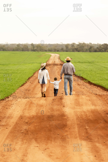 Back view of a family walking hand in hand on down a dirt road wearing cowboy hats