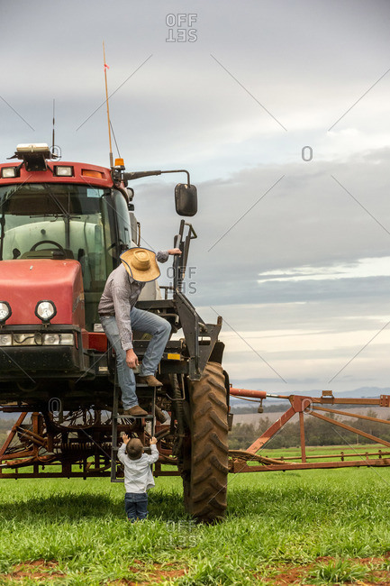 Farmer standing on steps of his tractor reaching down to pick up toddler son
