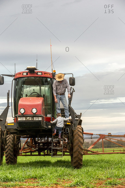 Little boy climbing up steps onto a tractor with his father
