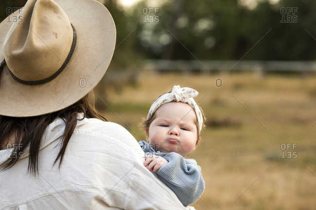 Adorable baby girl pouting her lips as she is carried in a field by her mother