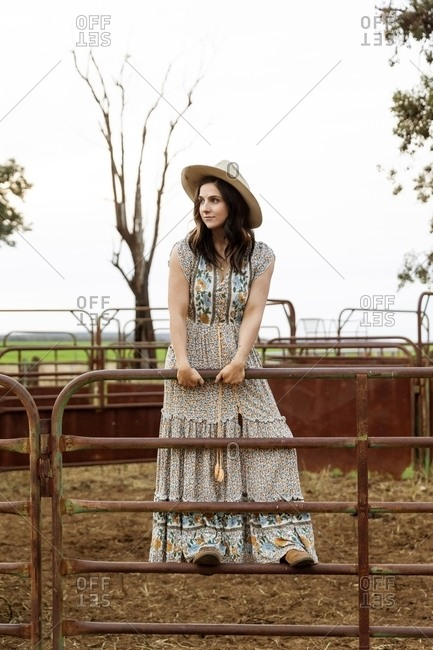 Young woman standing on a gate on a ranch