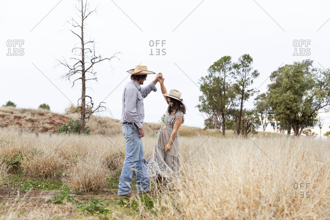 Young couple wearing cowboy hats dancing in a field